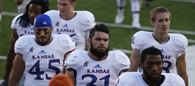 Kansas linebacker Ben Heeney (31), fullback Nick Sizemore (45), receiver Christian Matthews (12) and the rest of the Jayhawks leave the field following their 35-13 loss to Texas on Saturday, Nov. 2, 2013 at Darrell K. Royal Stadium in Austin, Texas.