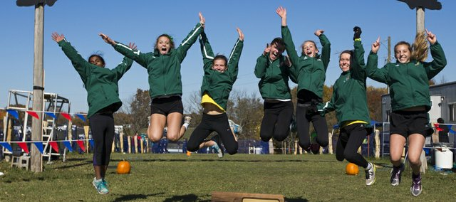 Members of the Free State girls cross county team jump in the air after placing first in the 2013 Girls 6A State Cross Country Championship, held at Rim Rock Farm Saturday morning.