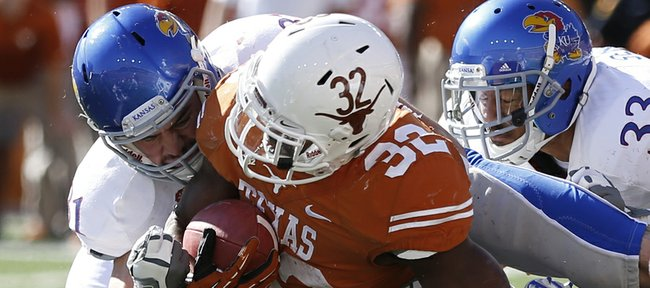 Kansas linebackers Ben Heeney, top left, and Jake Love (57) bring down Texas running back Johnathan Gray short of a first down with the help of safety Cassius Sendish during the second quarter on Saturday, Nov. 2, 2013 at Darrell K. Royal Stadium in Austin, Texas.