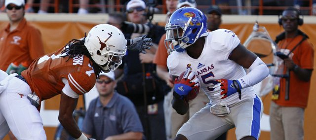 Kansas safety Isaiah Johnson is looks to break away from Texas receiver Marcus Johnson after intercepting a pass during the fourth quarter on Saturday, Nov. 2, 2013 at Darrell K. Royal Stadium in Austin, Texas. Johnson intercepted two passes in the 35-13 loss.