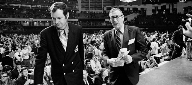 In this file photo from March 25, 1971, Kansas University basketball coach Ted Owens, left, and UCLA coach John Wooden walk from the Astrodome after UCLA defeated Kansas, 68-60, in the NCAA Tournament semifinal game in Houston.
