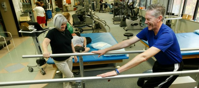 Lawrence resident Sam Porritt laughs while working on strengthening exercises with Lawrence Memorial Hospital physical therapist Karen Bayouth on Wednesday. Porritt, who is making a comeback from paralysis below the waist after falling from a ledge in Italy in 2011, has created the Falling Forward Foundation to assist those in recovery situations like his with paying the cost of rehabilitation that insurance will not cover.