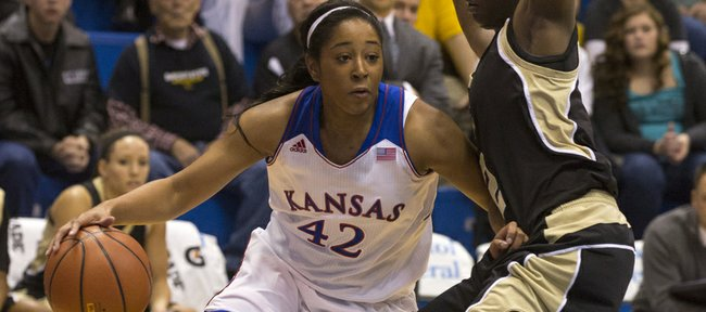 Kansas guard Natalie Knight (42) uses her off hand to create space as she drives past Emporia State's Kelly Moten (2) during their exhibition game, Sunday afternoon at Allen Fieldhouse. The Jayhawks downed the Hornets 61-53 in their final exhibition game of the season. Kansas opens its season next Sunday, Nov. 10, at home against Oral Roberts.