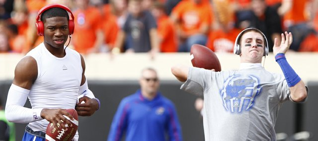 Kansas quarterbacks Montell Cozart, left, and Jake Heaps warm up prior to kickoff against Oklahoma State on Saturday, Nov. 9, 2013 at Boone Pickens Stadium in Stillwater, Oklahoma.