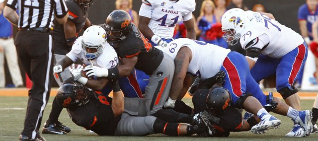Kansas running back James Sims is brought down for a loss by Oklahoma State defenders Tyler Johnson and James Castleman, bottom, during the second quarter on Saturday, Nov. 9, 2013 at Boone Pickens Stadium in Stillwater, Oklahoma.