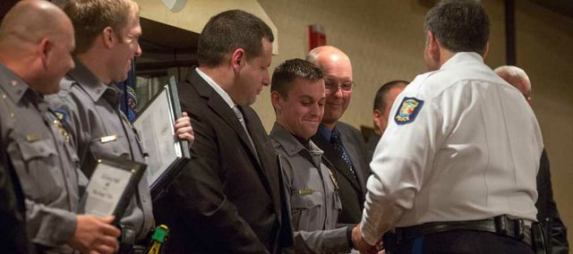 Lawrence police officer Peter Kirby smiles as she shakes the hand of Lawrence police chief Tarik Khatib after Officer Kirby received a Life Saving Award, Thursday night at the Holidome.