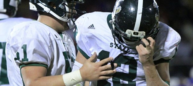 Free State's Joe Dineen (12) is consoled in the final minutes of the Firebirds' 22-18 loss to Olathe North on Friday, Nov. 15, 2013, in Olathe.