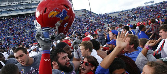 Kansas linebacker Ben Heeney is mobbed by fans following the Jayhawks' 31-19 win over West Virginia on Saturday, Nov. 16, 2013 at Memorial Stadium.