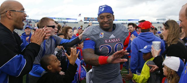 Kansas running back James Sims runs off the field to the hearty applause of Jayhawk fans following the Jayhawks' 31-19 win over West Virginia on Saturday, Nov. 16, 2013 at Memorial Stadium.