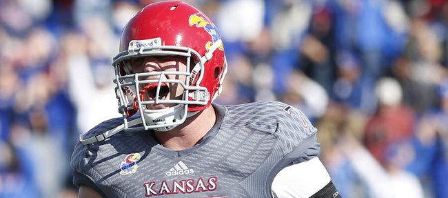 Kansas offensive lineman Riley Spencer celebrates a touchdown by running back James Sims against West Virginia during the third quarter on Saturday, Nov. 16, 2013 at Memorial Stadium.