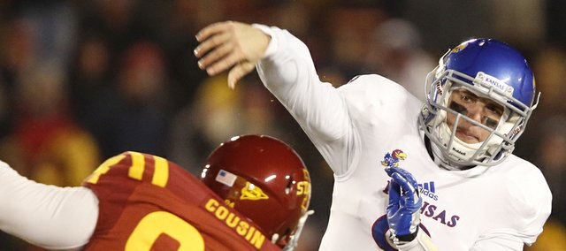 Kansas quarterback Jake Heaps throws over Iowa State defensive lineman Devlyn Cousin during the fourth quarter on Saturday, Nov. 23, 2013 at Jack Trice Stadium in Ames, Iowa.