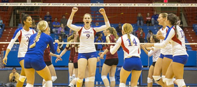 Kansas' Caroline Jarmoc (9) pumps her fist in the air after making a kill during Kansas' volleyball match against Denver Tuesday evening at Allen Fieldhouse. The Jayhawks won the match, 3-1.