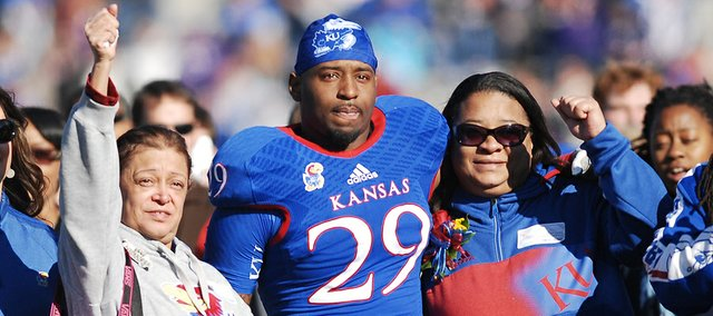 Kansas University senior running back James Sims (29) stands with his grandmother, Juana Luna, left, and his mother, Mary Luna, as they watch a video of Sims during senior day recognition before the Jayhawks' game against Kansas State, Saturday at Memorial Stadium.