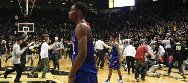 Kansas guard Andrew Wiggins, front, and Frank Mason leave the court following a game-winning three pointer by Colorado guard Askia Booker on Saturday, Dec. 7, 2013 at the Coors Events Center in Boulder, Colorado.