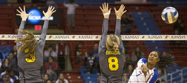 Kansas' Tiana Dockery (7) sends a shot past Wichita State's Elizabeth Field (3) and Chelsey Feekin (8) during their volleyball match in the first round of the NCAA tournament at Allen Fieldhouse. The Jayhawks defeated the Shockers, 3-1, and will face Creighton Saturday at 6:30 p.m.