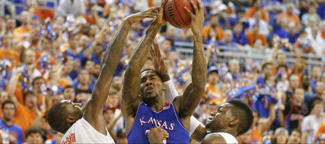 Kansas forward Jamari Traylor gets knocked around by Florida defenders Dorian Finney-Smith, left, and Will Yeguete during the second half on Tuesday, Dec. 10, 2013 at O'Connell Center in Gainesville, Florida.
