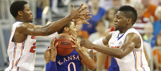 Kansas guard Frank Mason is caught between Florida defenders Michael Frazier II, left, and Will Yeguete during the first half on Tuesday, Dec. 10, 2013 at O'Connell Center in Gainesville, Florida.
