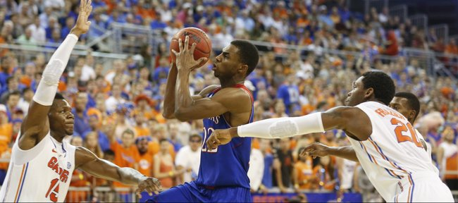Kansas guard Andrew Wiggins heads to the bucket between Florida defenders Will Yeguete, left, and Michael Frazier II during the second half on Tuesday, Dec. 10, 2013 at O'Connell Center in Gainesville, Florida.