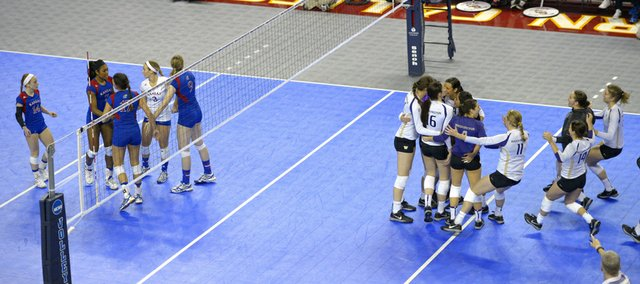 Members of the Washington volleyball team, right, celebrate after defeating Kansas University in the NCAA Tournament, Friday, Dec. 13, 2013, in Los Angeles.