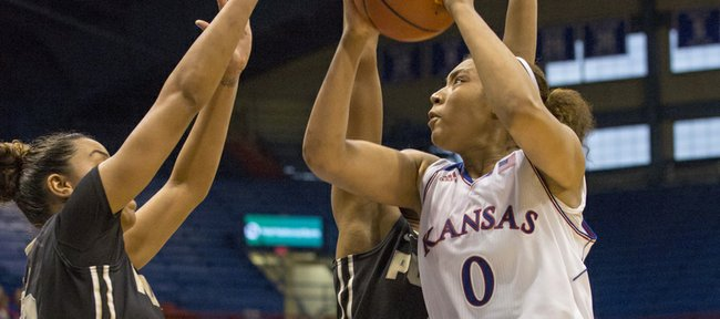 Kansas junior guard Asia Boyd (0) tries to give the Jayhawks the lead with seconds remaining in the game against a Purdue double-team by Liza Clemons, left, and Camille Redmon during their game Sunday afternoon at Allen Fieldhouse. The Jayhawks came up short against the Boilermakers, losing 71-68.