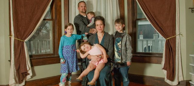 Tresa McAlhaney, a Lawrence native, is running for governor in 2014 as a libertarian. She is pictured holding daughter Emma, 2, at the family's Bonner Springs home on a recent day with, from left, daughter Natalie, 12, husband Michael, 10-month-old daughter Maegan, and son Logan, 8.