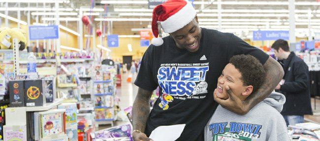 Kansas forward Jamari Traylor goofs around with a young fan while shopping for charity Thursday, Dec. 19, 2013, at Wal-Mart on Iowa Street.