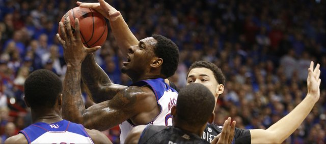 Kansas forward Tarik Black cuts through the Georgetown defense for a bucket and a foul during the first half on Saturday, Dec. 21, 2013 at Allen Fieldhouse.