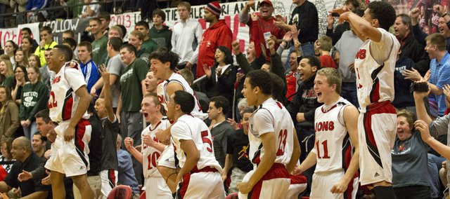 The Lawrence High bench erupts in celebration as a reserve hits a shot at the end of their game against Free State, Friday at LHS.