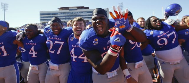 Kansas defensive lineman Keon Stowers hams it up for the cameras as the Jayhawks celebrate their 13-10 win over Louisiana Tech on a walk-off fieldgoal from kicker Matthew Wyman, Saturday, Sept. 21, 2013 at Memorial Stadium.