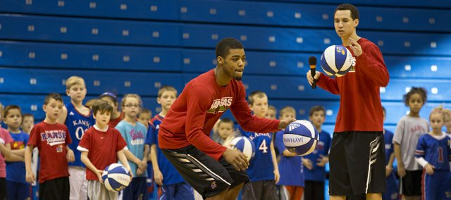 Kansas freshman guard Frank Mason demonstrates a crossover dribbling drill while teammate Evan Manning speaks to campers during KU men's basketball's annual holiday clinic, Saturday, Dec. 28, 2013, at Allen Fieldhouse. Participants went through drills with the team and then were able to get autographs.