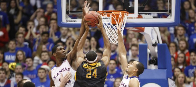 Kansas defenders Joel Embiid, left, and Perry Ellis defend against a shot from Toledo forward J.D. Weatherspoon during the first half on Monday, Dec. 30, 2013 at Allen Fieldhouse.