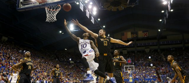 Kansas guard Naadir Tharpe glides under Toledo center Nathan Boothe for a bucket during the second half on Monday, Dec. 30, 2013 at Allen Fieldhouse.