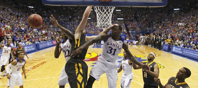 Kansas players Jamari Traylor (31) and Andrew Wiggins battle in the paint for a rebound with Toledo center Nathan Boothe during the second half on Monday, Dec. 30, 2013 at Allen Fieldhouse.