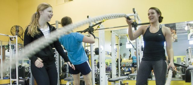 Jenny Siegel, training manager at Body Boutique, 2330 Yale Road, left, instructs Brittany Bettenbrock, right, in some alternating wave rope exercises during a workout Monday.