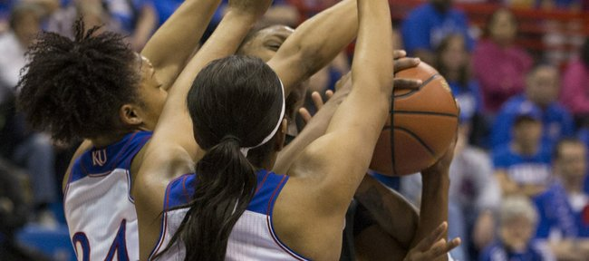 Kansas guards Natalie Knight (42), CeCe Harper (24) and Keyla Morgan, right, collapse around Texas Tech guard Amber Battle during their game, Saturday evening at Allen Fieldhouse.