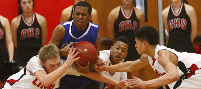 Rockhurst's Cartier Dean (13) gets swamped by Lawrence High defenders in the first half of a 71-64 Lions boys basketball victory, Saturday, Jan. 11, 2014, at LHS.