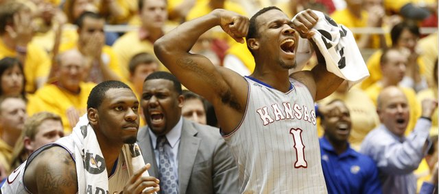 Kansas guard Wayne Selden flexes his muscles after a bucket by center Joel Embiid and a foul by Iowa State during the second half on Monday, Jan. 13, 2014 at Hilton Coliseum in Ames, Iowa. At left is Kansas forward Tarik Black and in back is assistant coach Jerrance Howard.