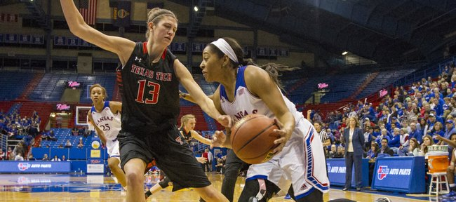 Kansas junior guard Natalie Knight tries to drive past Texas Tech center Kellyn Schneider (31) along the baseline during their game, Saturday evening at Allen Fieldhouse.