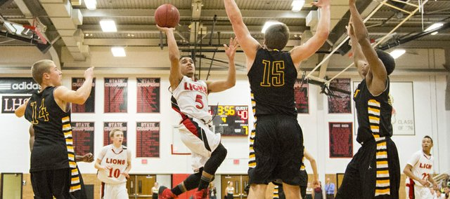 Lawrence High sophomore Justin Roberts (5) hangs in the air as he scores against Shawnee Mission West defenders Zach Witters (14), Justin Fetzer (15) and Louis Rollins, right, during their game, Tuesday at LHS. The Lions boys won, 64-50.