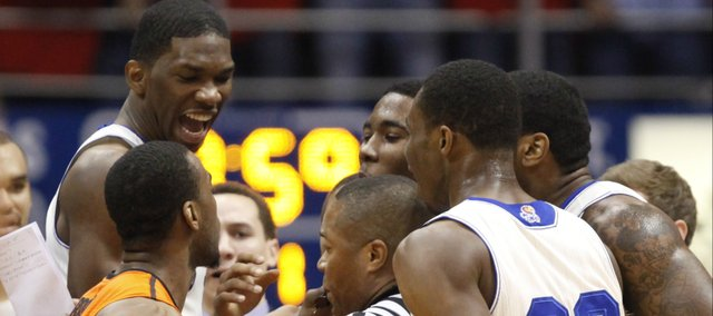 Kansas players celebrate as Oklahoma State guard Markel Brown breaks into their huddle during the first half on Saturday, Jan. 18, 2014 at Allen Fieldhouse. Brown was issued a technical foul during the incident.