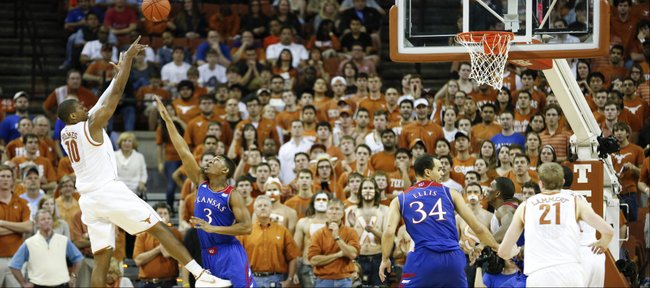 Texas forward Jonathan Holmes turns for a shot over Kansas guard Andrew White during the first half on Saturday, Feb. 1, 2014 at Erwin Center in Austin, Texas.