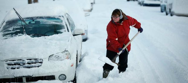 Emily Barber shovels away snow from her vehicles' tires on Wednesday morning as the city digs itself out from the snow storm.