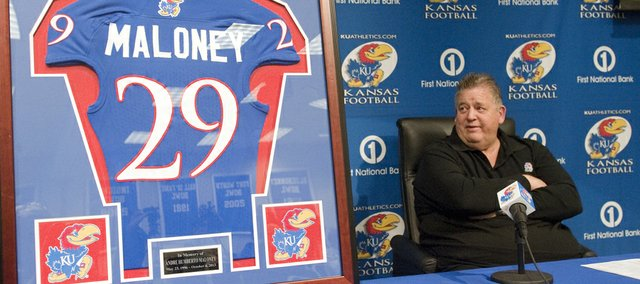Kansas University football coach Charlie Weis glances as a framed KU jersey in memory of Andre Maloney, a Shawnee Mission West senior who had orally committed to Kansas before he suffered a stroke and died in a game this past October.