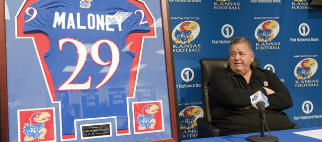 Kansas University football coach Charlie Weis glances as a framed KU jersey in memor
