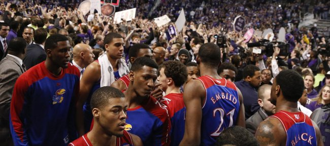 Kansas guard Frank Mason, front, and his teammates look for an exit from the court as the Kansas State student section celebrate following the Jayhawks' 85-82 overtime loss to Kansas State on Monday, Feb. 10,