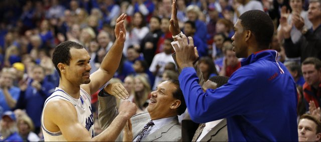 Kansas forward Perry Ellis gets a round of high fives from his teammates and coaches as he leaves the game after a 32-point effort against TCU on Saturday, Feb. 15, 2014 at Allen Fieldhouse.