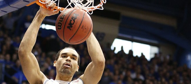 Kansas forward Perry Ellis delivers a dunk before TCU forward Amric Fields during the first half on Saturday, Feb. 15, 2014 at Allen Fieldhouse.