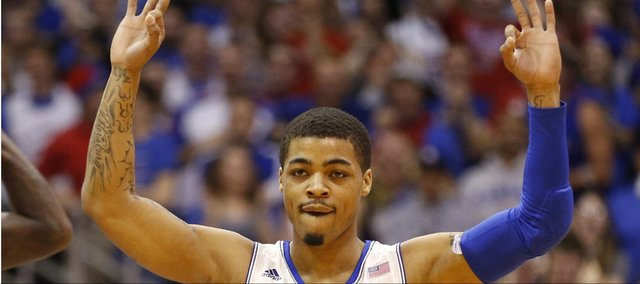 "Kansas guard Frank Mason signals ""three"" after a three-pointer by teammate Andrew Wiggins during the first half on Saturday, Feb. 22, 2014 at Allen Fieldhouse."