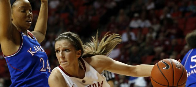 Oklahoma's Morgan Hook (10) drives past Kansas' CeCe Harper (24) during an NCAA college basketball game Saturday, Feb. 22, 2014, in Norman, Okla. (AP Photo/The Oklahoman, Steve Sisney)