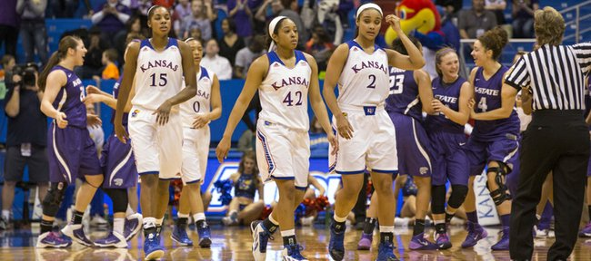 Kansas players Chelsea Gardner (15), Natalie Knight (42) and Dakota Gonzalez (2) walk off the court as Kansas State players celebrate behind them following Kansas' loss to KSU, Wednesday evening at Allen Fieldhouse.